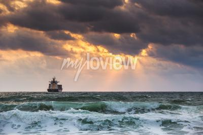 Fototapet Sun inställning på havet med segel lastfartyg