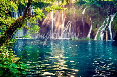 Fototapet Det sista solstrålet lyser upp det rena vattenfallet på Plitvice National Park